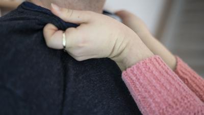 Frauenhände packen einen Mann am Kragen.
