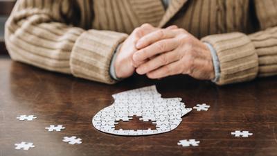 Mann setzt Puzzle in Form eines Kopfes zusammen, das Lücken aufweist.