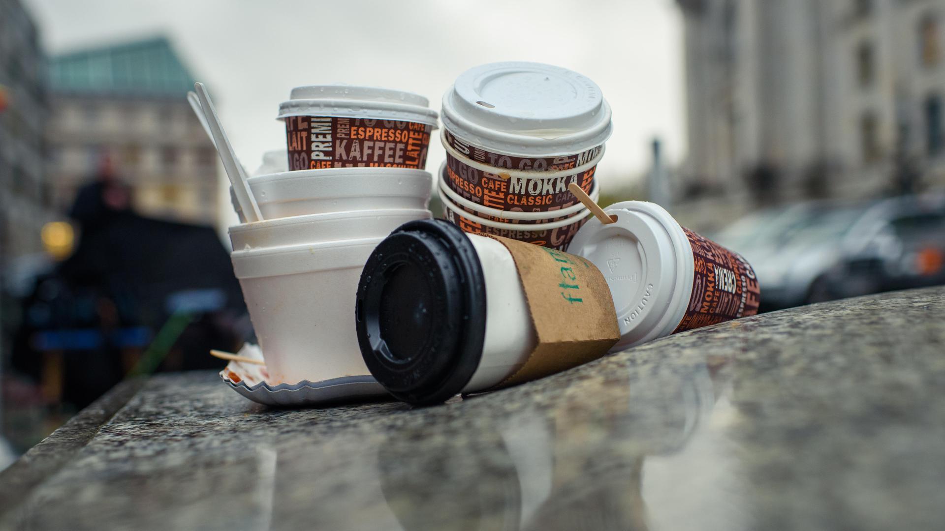 Leere Einweg-Kaffeebecher und Plastikschalen stapeln sich an einem Gehweg.