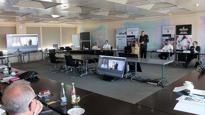 Der Kreisfeuerwehrverband tagt in einem Sitzungssaal. Auf einer Leinwand ist auch Landrat Christoph Schnaudigel zugeschaltet.