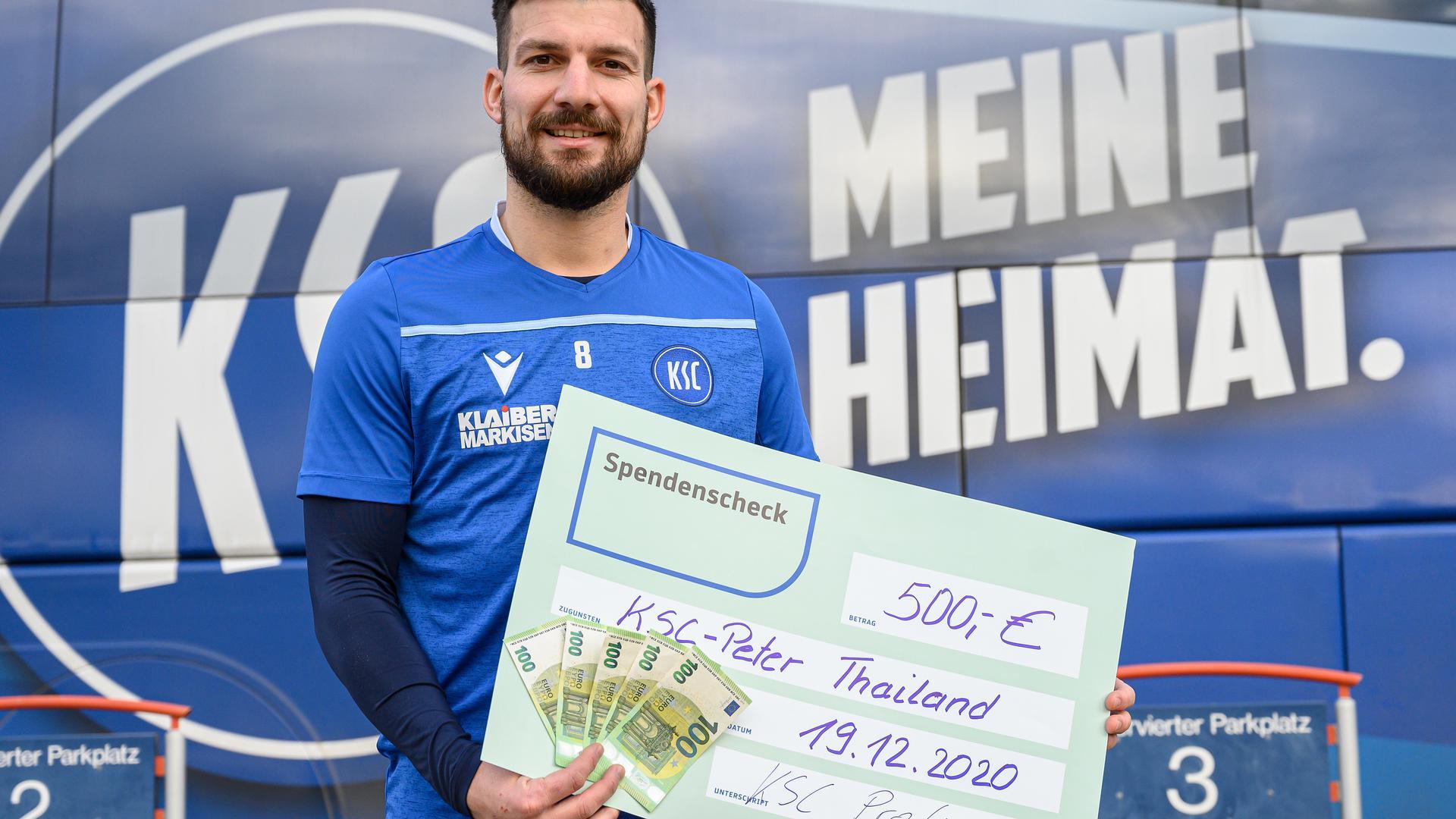 Spielführer Jerome Gondorf (KSC) mit Spendenscheck.