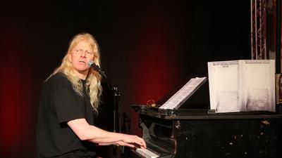 Der Mann am Klavier ist Musiker, Kabarettist, Puppenspieler und mittlerweile sogar professioneller Bühnenpyrotechniker: Gunzi Heil. Das Foto entstand am 6. März 2020 kurz vor dem ersten Lockdown bei der Eröffnung einer Ausstellung von Timm Ulrichs in Berlin.