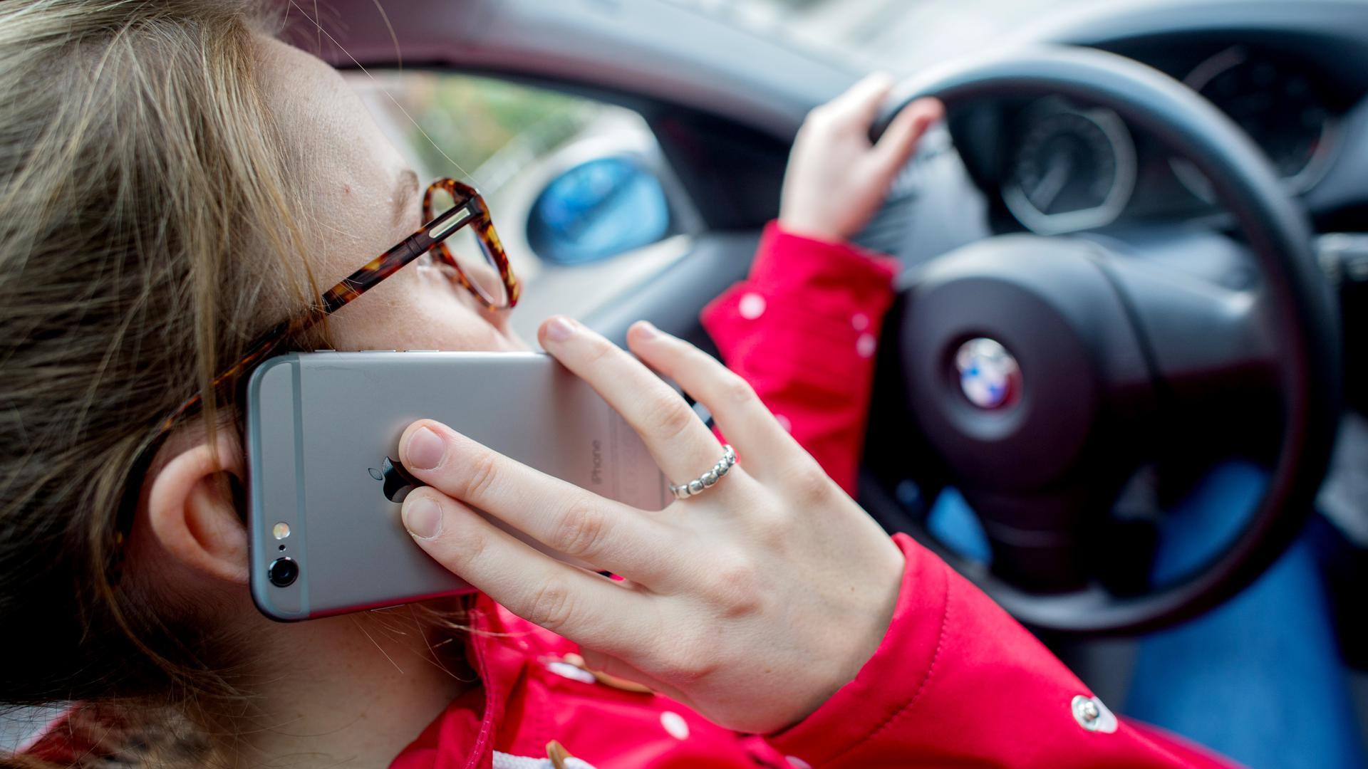 Eine junge Frau sitzt in einem Auto am Steuer und telefoniert mit ihrem Smartphone.