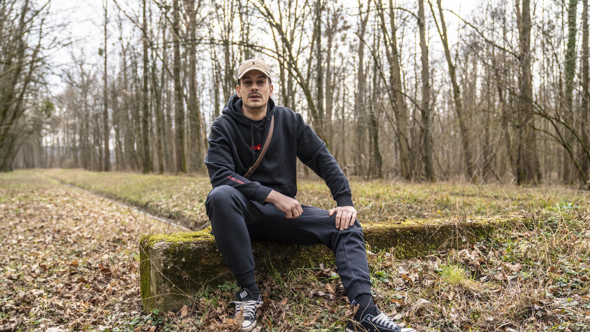 David Bošnjak, besser bekannt als Haze, sitzt auf einem Stein, hinter ihm ist ein Waldstück zu erkennen.