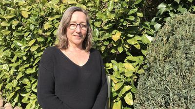 Helga Beisel steht in in ihrem Garten.