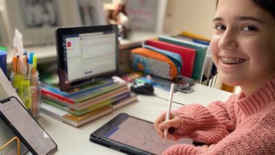 Mädchen sitzt am Schreibtisch mit Tablets