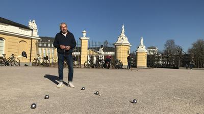 Mann steht auf einem Boule-Feld