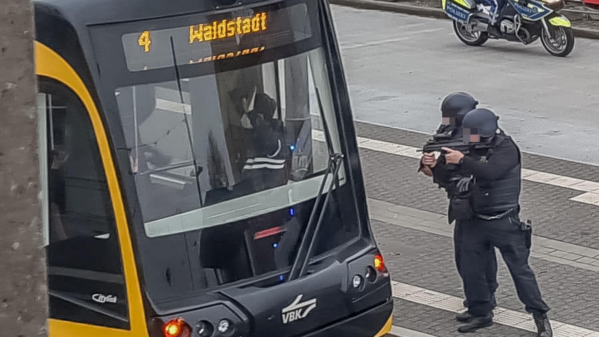 Zwei Polizisten stellen eine Person, die in einer Straßenbahn steht.