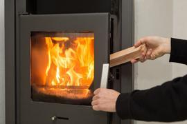 In einem Kaminofen brennt ein Feuer. Eine Hand öffnet die Ofentür, eine andere Hand legt einen Holzscheit nach.