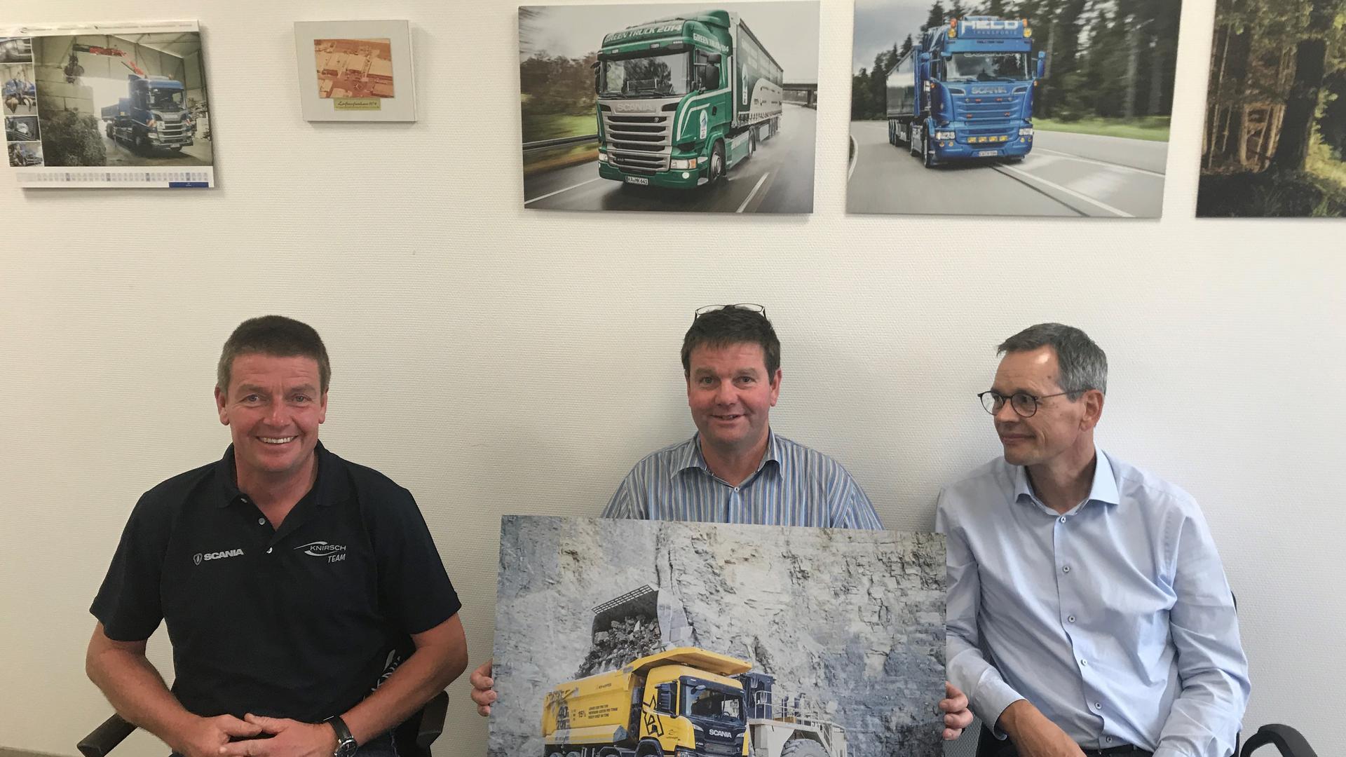Drei Männer mit Lastwagenkalender