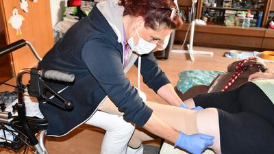 Altenpflegerin Martina Winkendick zieht einer Patientin Kompressionsstrümpfe an.