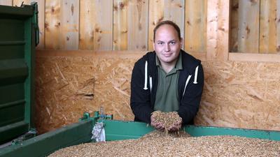 Landwirt Tobias Holstein hält Dinkel in seinen Händen.