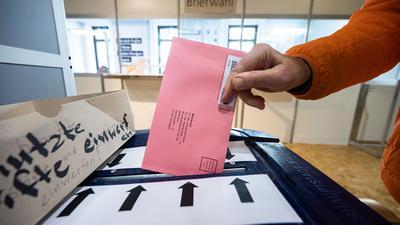 Ein Briefwähler steckt im Rathaus Stuttgart seinen Wahlbrief in eine Wahlurne.