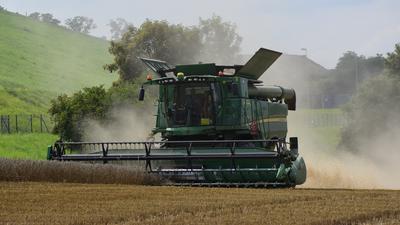 Ein Mähdrescher fährt über ein Feld und holt die Ernte ein.
