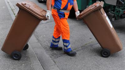 """ARCHIV - 31.07.2012, Baden-Württemberg, Freiburg: Ein Mitarbeiter der Abfallwirtschaft und Stadtreinigung schiebt eine braune Tonne mit Biomüll zum Müllwagen. (zu dpa: «Kommunen wollen Steuern und Gebühren erhöhen"""") Foto: Patrick Seeger/dpa +++ dpa-Bildfunk +++   Verwendung weltweit"""