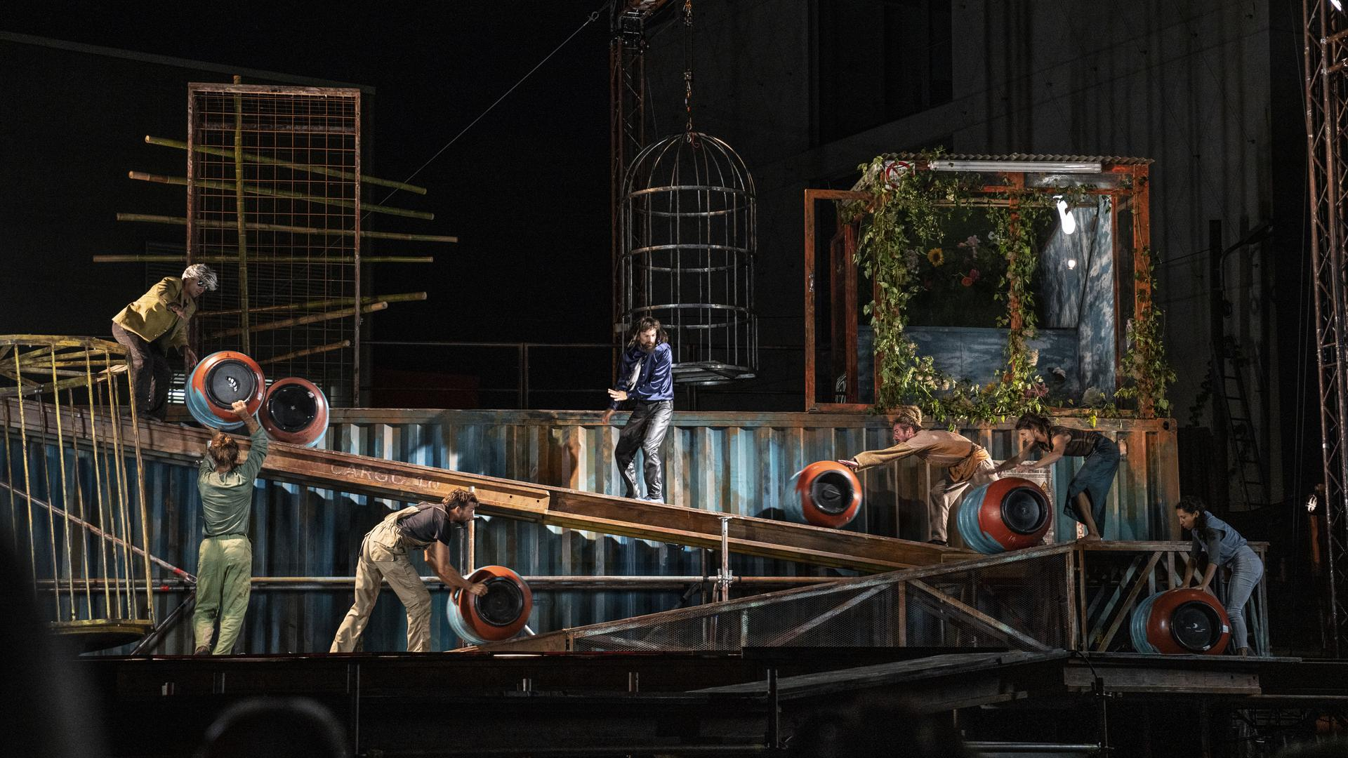 Blaue Fässer rollen über die Bühne