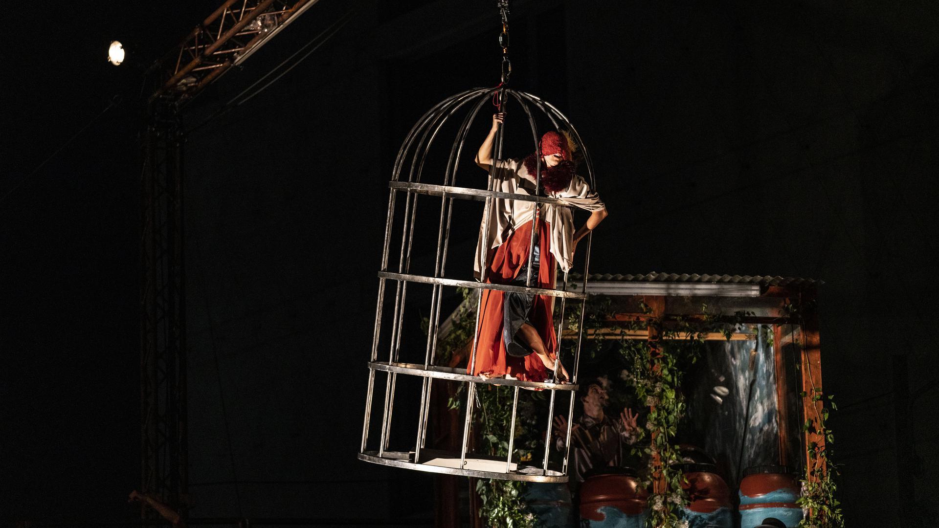 Eine Frau steht in einem Käfig
