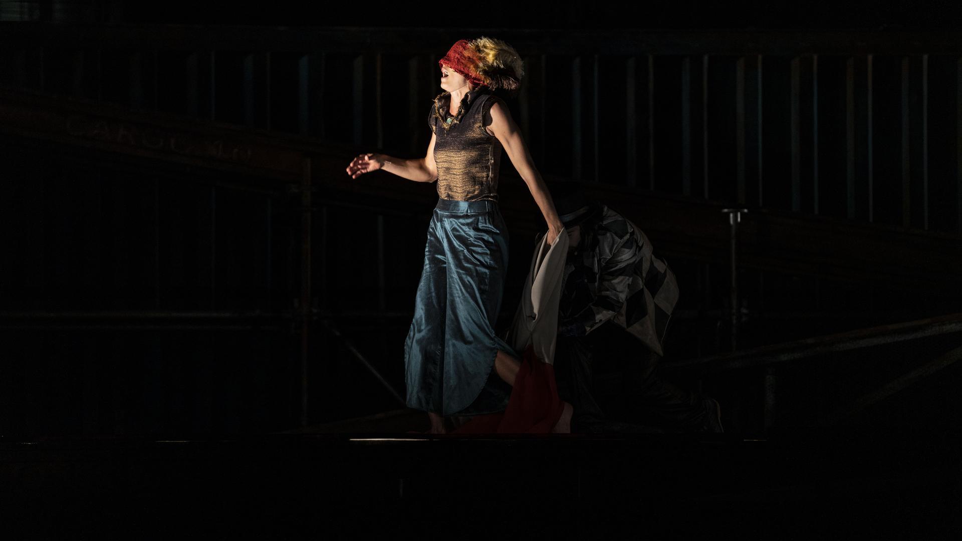 Eine Frau mit verbundenen Augen singt auf der Bühne.