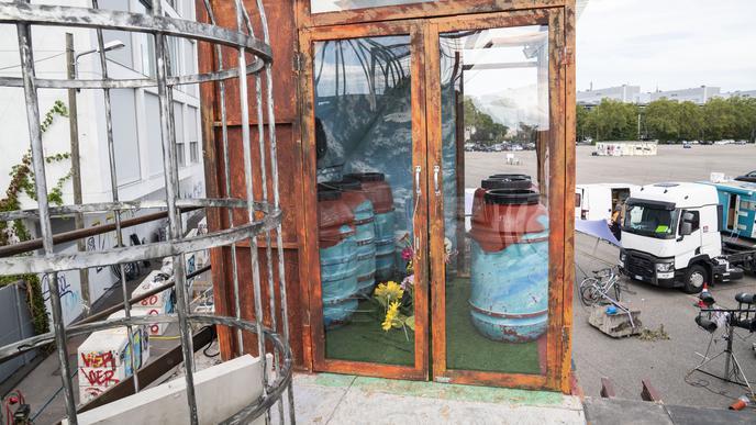 Bemalte Fässer stehen in einer Kabine