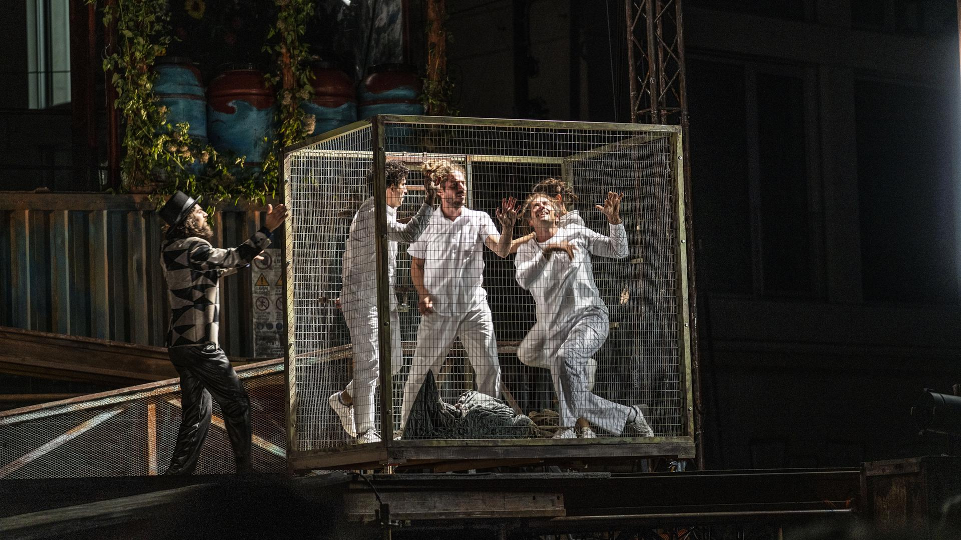 Menschen stehen in einem Käfig
