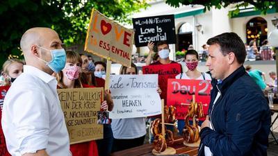 Christian Merkel (links) steht Steve Alter (rechts) gegenüber. Im Hintergrund Demonstranten mit Plakaten und Schildern.