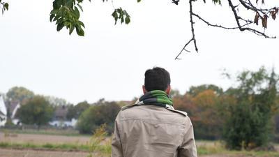 Mirco Schmitz ist von hinten zu sehen. Er blickt in Richtung Feld.