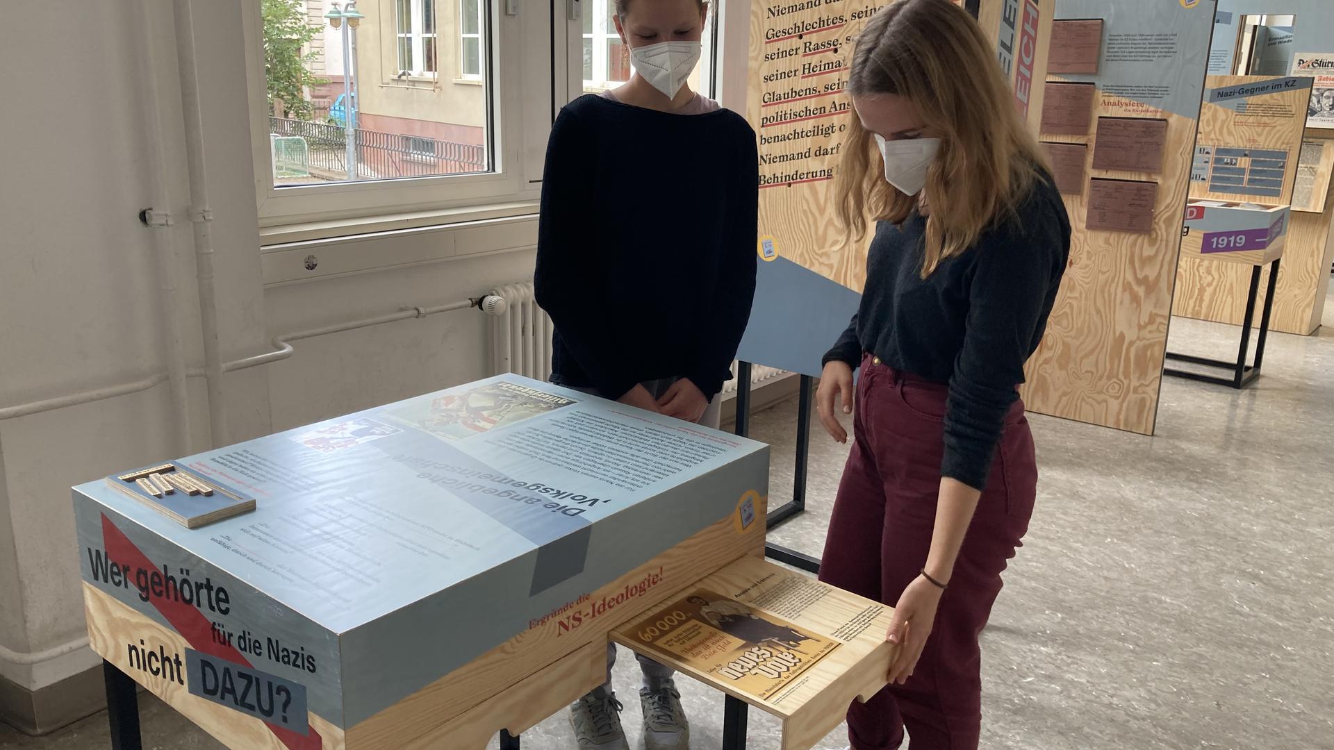 Die Peer-Guides Mathea Nägeli (links) und Laura Pastal zeigen eine Station des mobilen Geschichtslabors.