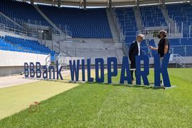 """Der neue Name """"BBBank Wildpark"""" steht mit Zeichen auf dem Rasen im KSC-Stadion."""