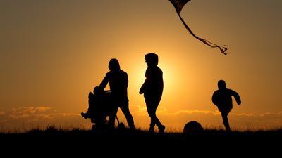 Schattenriss von einer Familie vor einem Sonnenuntergang