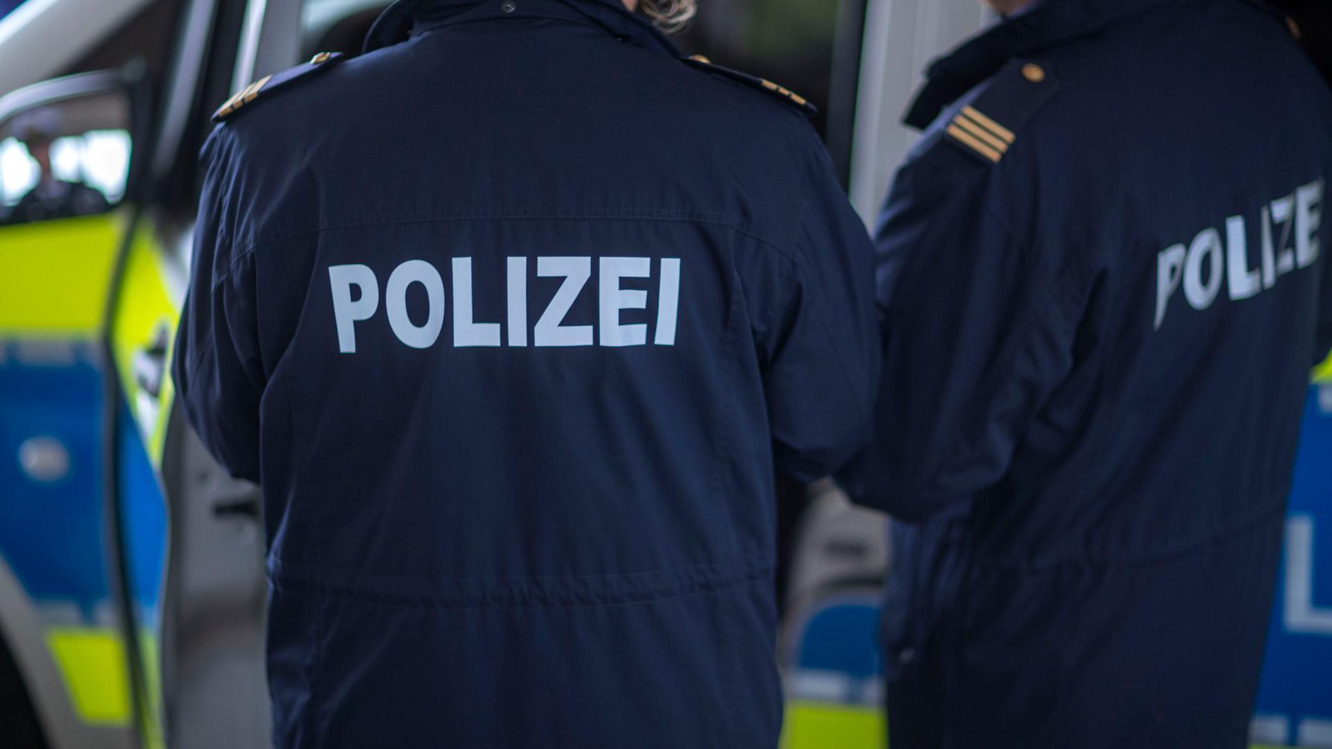 Polizisten stehen vor einem Polizeifahrzeug.