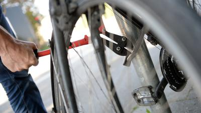 """ARCHIV - ILLUSTRATION - Ein Mann versucht am 14.09.2016 in München (Bayern) mit einem Bolzenschneider ein Fahrradschloss aufzubrechen (gestellte Szene). Fahrraddiebstahl hat die deutschen Hausratversicherer im vergangenen Jahr 120 Millionen Euro gekostet. Das ist die höchste Summe seit 1998, als der Gesamtverband der Deutschen Versicherungswirtschaft die Summe erstmals ausrechnete. (zu dpa """"Fahrraddiebstähle kosten Versicherer Rekordsumme"""" vom 12.06.2017) Foto: Andreas Gebert/dpa +++ dpa-Bildfunk +++"""
