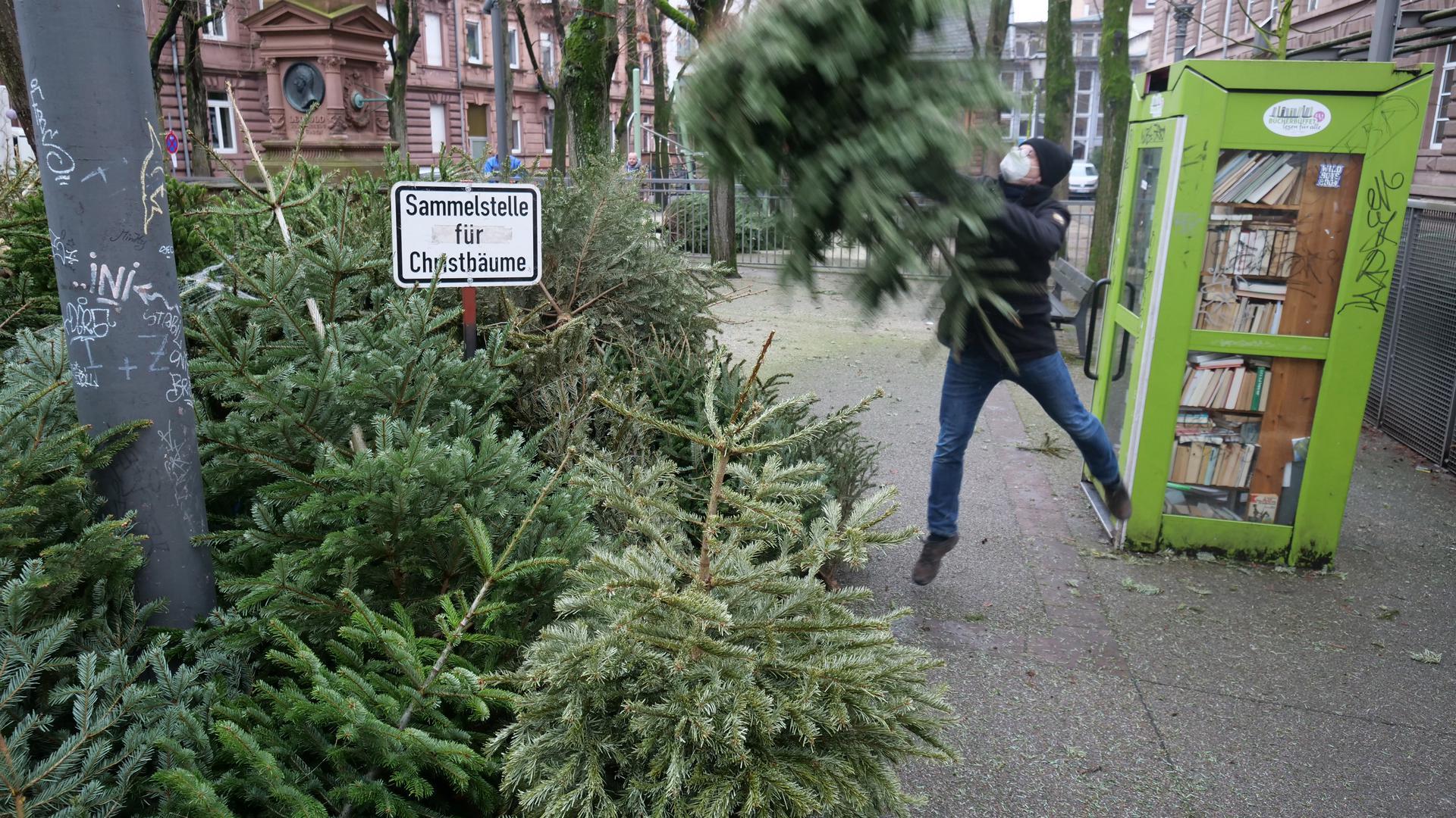 Ein Mann wirft seinen Christbaum auf die Sammelstelle.
