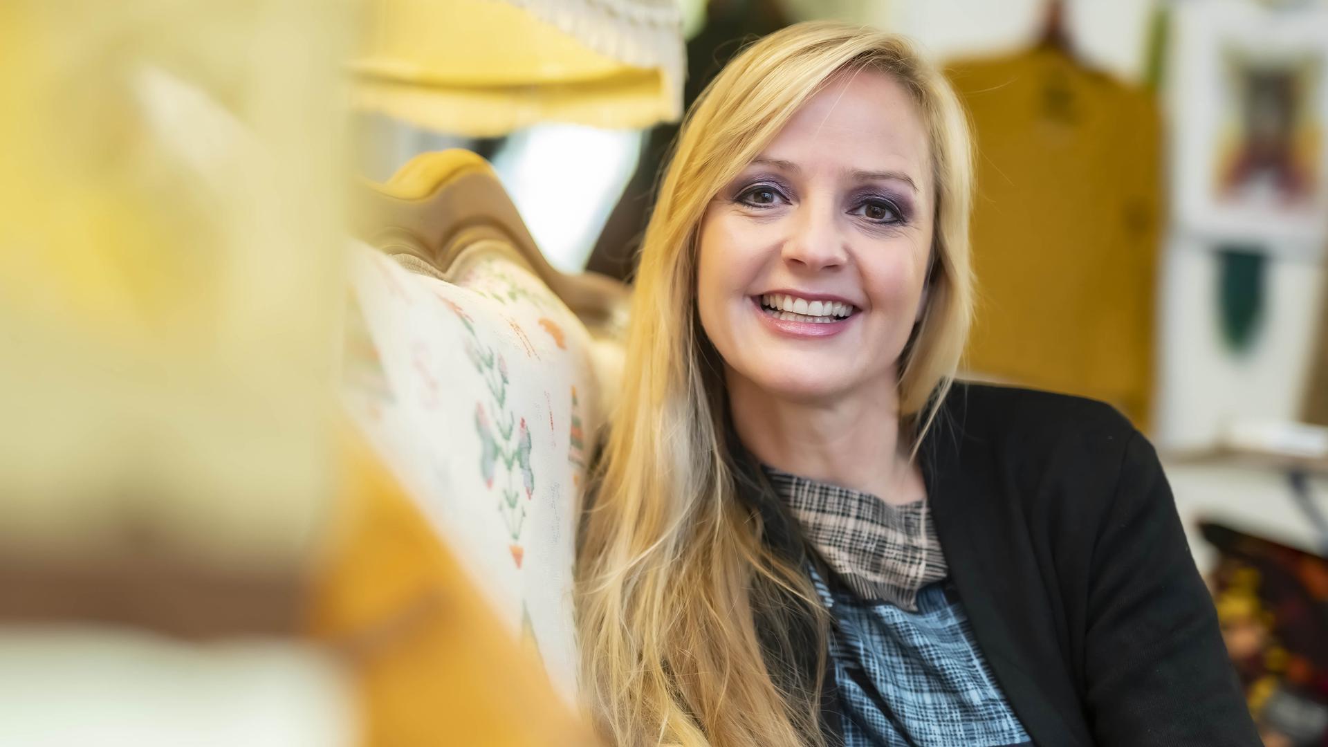 """Sandie Wollasch auf dem Sofa im """"Laden zwei"""". Von hier aus präsentiert sie regelmäßig mit Rolf Ableiter """"Musik aus der Ladenecke""""."""