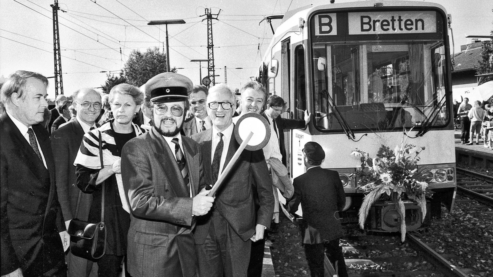 """Start-Signal: Verkehrsminister Hermann Schaufler schwingt bei der Stadtbahn-Premiere im Herbst 1992 die Bahn-Kelle. Ganz links: Dieter Ludwig, der Vater des """"Karlsruher Modells""""."""