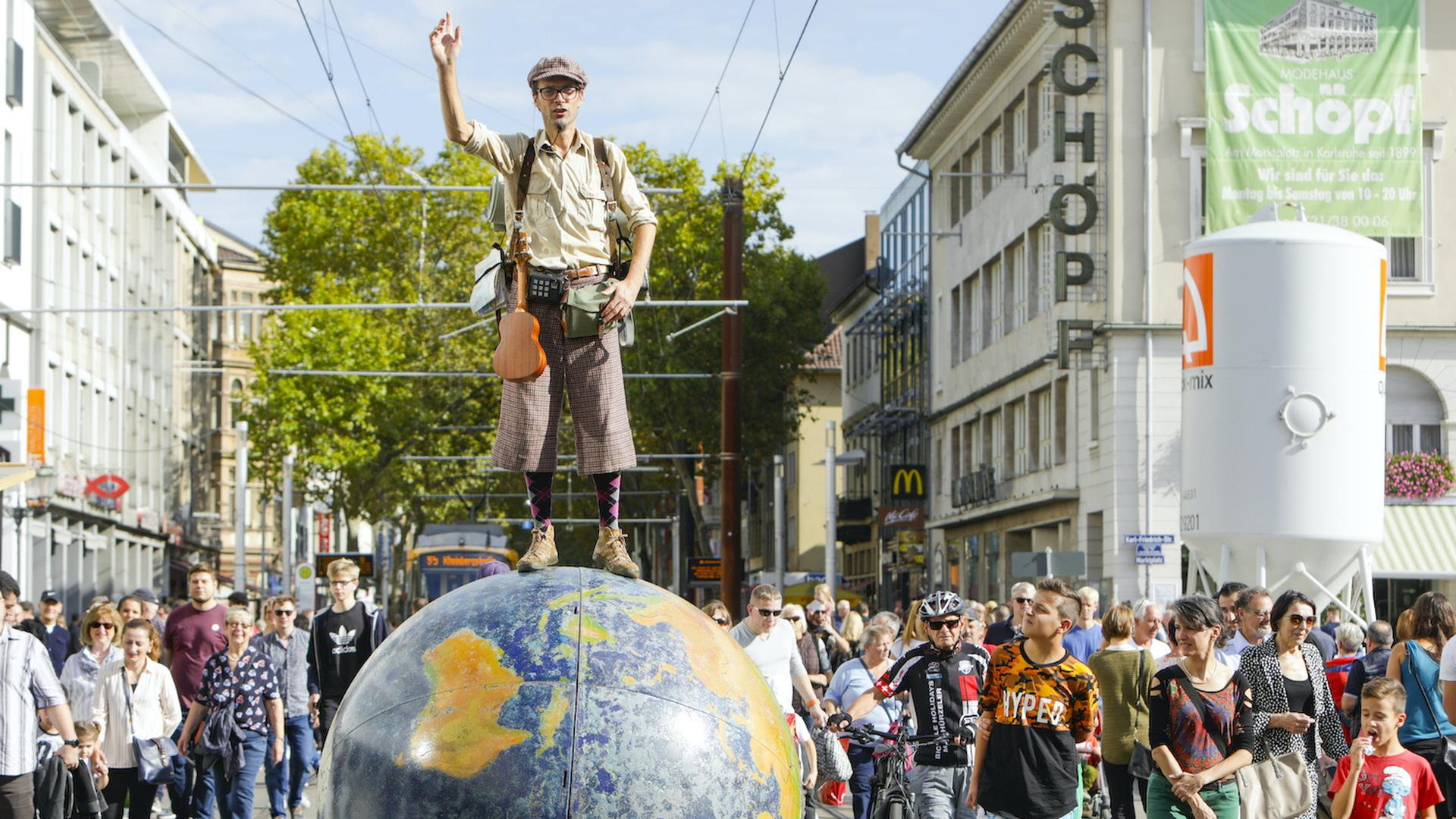 Mann auf Weltkugel ist in der Karlsruher Kaiserstraße unterwegs.
