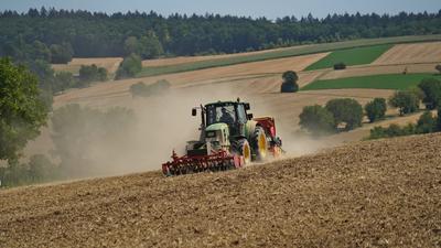 Ein Landwirt fährt mit seinem Traktor übers Feld. Vorne am Buldog hängt ein Frontpacker, hinten eine Sämaschine.