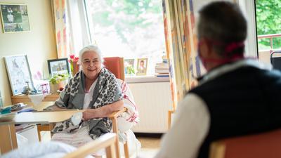 Fröhliche, alte Dame im Pflegeheim mit Besuch und Blumen.
