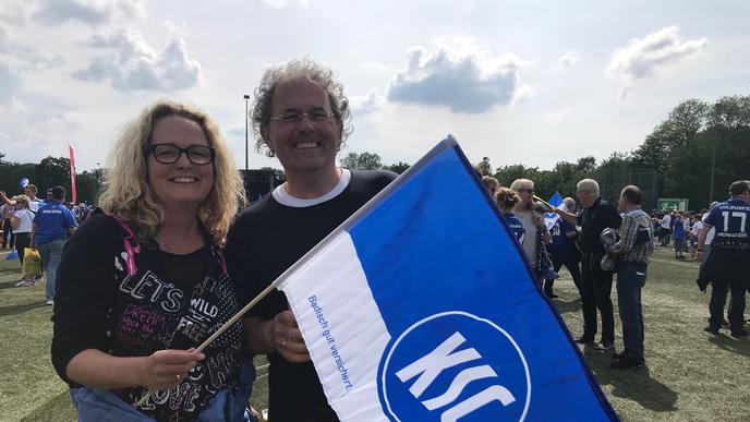 Fans halten eine KSC-Fahne in der Hand.