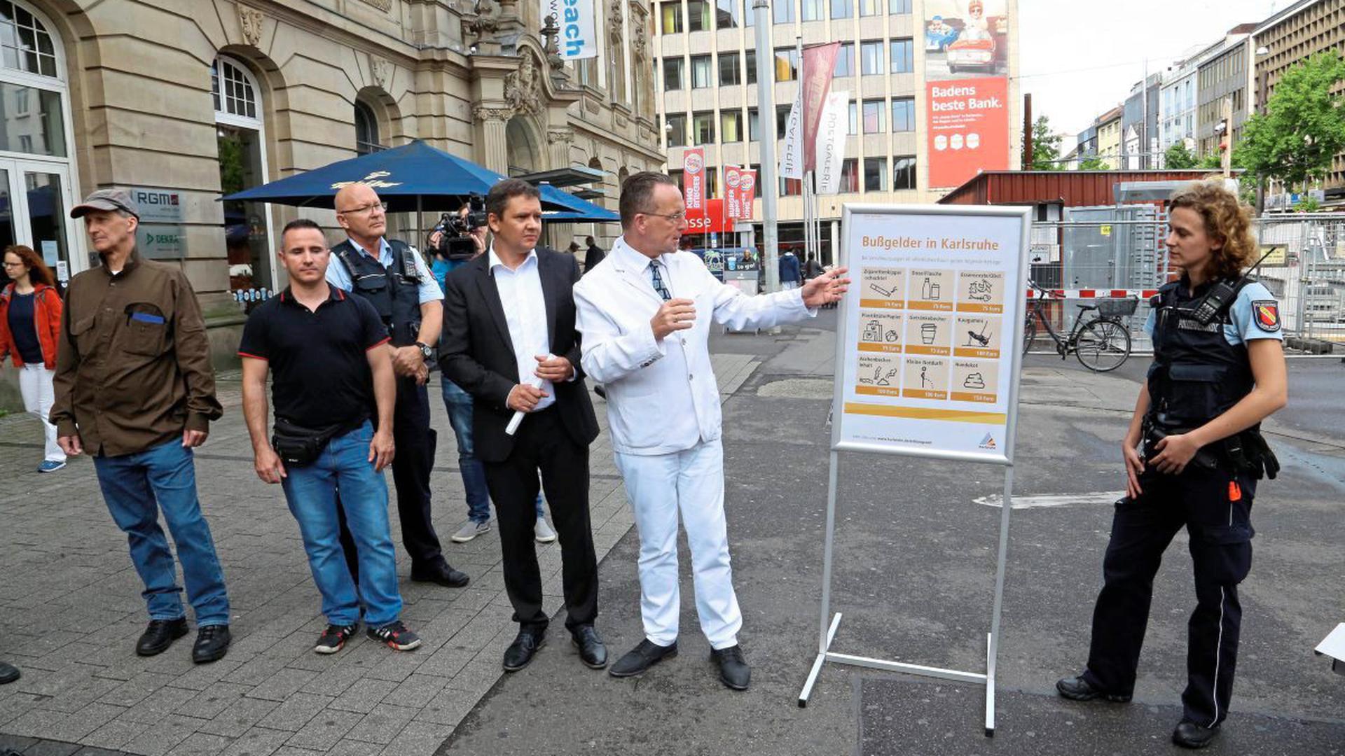 Wie teuer es ab sofort ist, in Karlsruhe Müll in die Gegend zu werfen und dabei erwischt zu werden, erklärten auf dem Europaplatz zwischen städtischen Ordnungskräften Bürgermeister Albert Käuflein und Ordnungsamtsleiter Björn Weiße (von rechts).