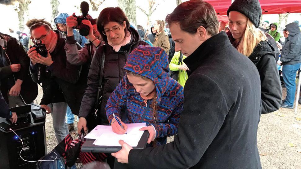 Franziska S. unterschreibt ihre Verfassungsbeschwerde.