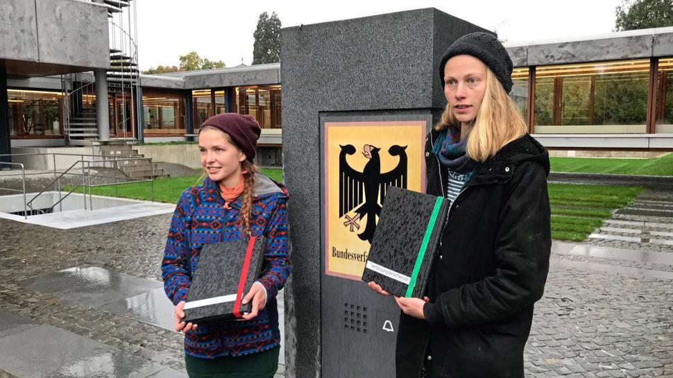 Franziska S. und Caroline K. werfen ihre Verfassungsbeschwerde in Form von zwei dicken Stapeln Papier am Karlsruher Bundesverfassungsgericht ein.
