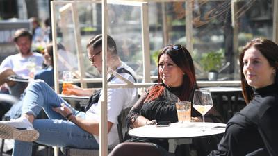 Streng getrennt: Hinter provisorischen Holzgerüsten mit Kunststoffscheiben genießen die Gäste dieses Lokals ihre Getränke. In Baden-Württemberg haben Restaurants und Gaststätten seit Montag wieder geöffnet. Die Wirte ziehen allerdings eine sehr durchwachsene erste Bilanz.