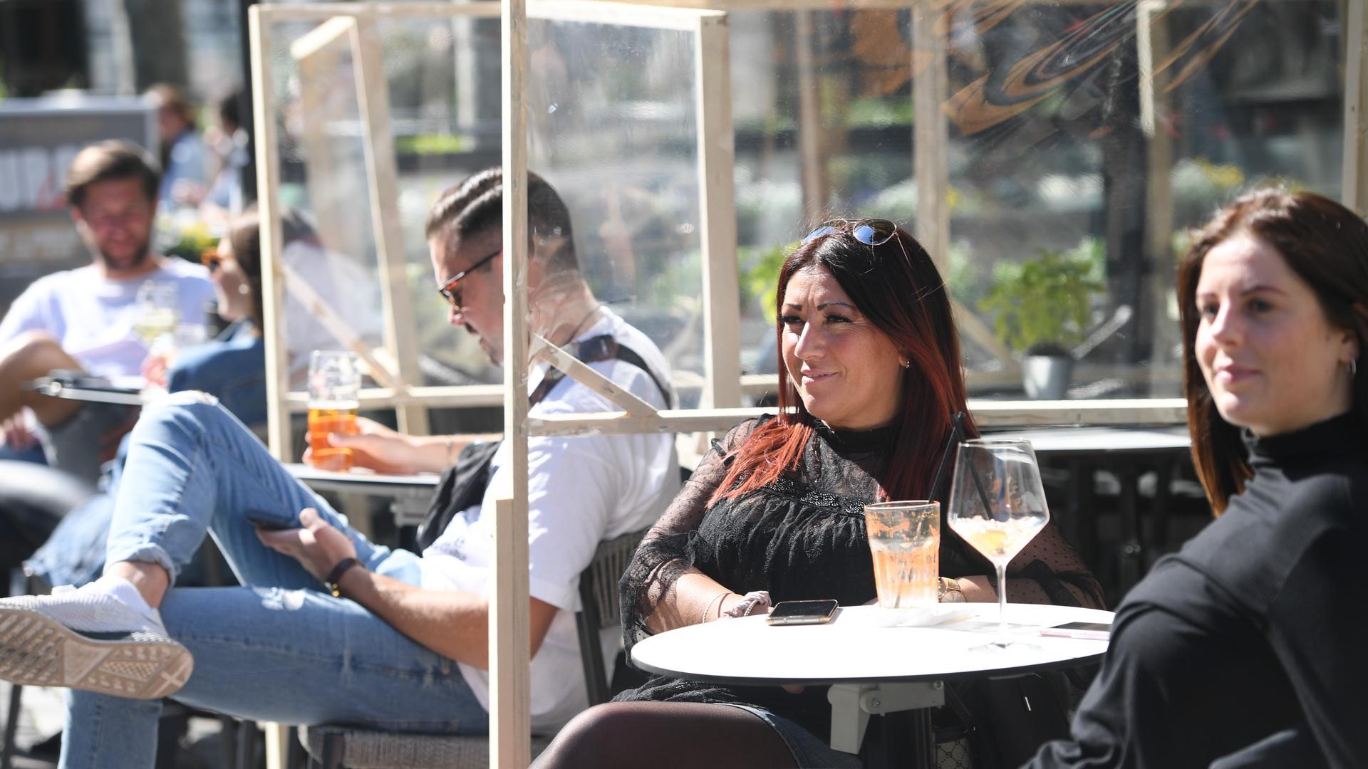 Streng getrennt: Hinter provisorischen Holzgerüsten mit Kunststoffscheiben genießen die Gäste dieses Lokals ihre Getränke. In Baden-Württemberg machen sich viele Wirte Sorgen um den Fortbestand ihrer von der Pandemie schwer getroffenen Betriebe.