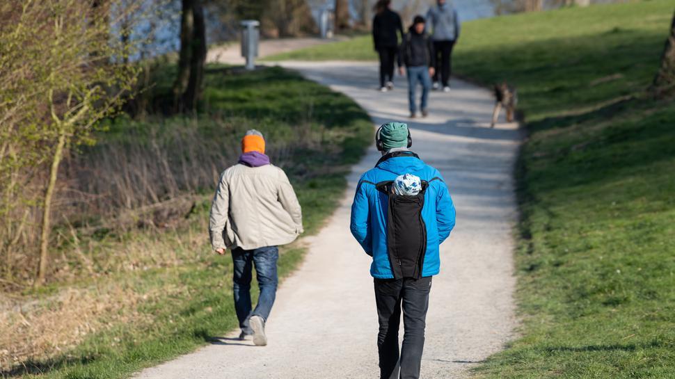 Menschen spazieren wegen des Coronavirus einzeln
