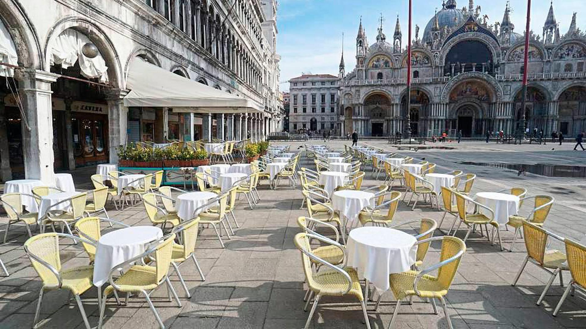 Leere Stühle und Tische stehen vor einem Restaurant auf dem Markusplatz in Venedig, wo nur noch sehr wenige Touristen unterwegs sind.