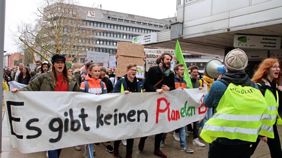Schüler demonstrieren. Sie halten ein Banner, einer trägt ein Megafon. Im Hintergrund das Pforzheimer Rathaus.