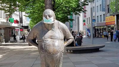 Eine Statue mit Mundschutz steht in der Fußgängerzone