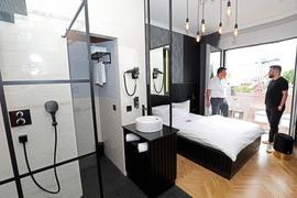 Schwarz-Weiß ist Trumpf: Afrim Bajrami (in Weiß), der Herr der Immobilie, und Steven Ockert, der Betreiber des Boutique Hotels, haben das Zimmer in ihren Farben stylish gestaltet. Dusche und Waschbecken sind im Raum.