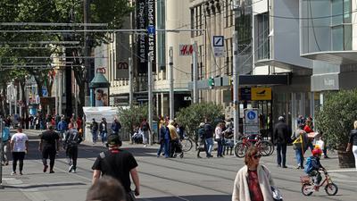 Trotz bestehender Einschränkungen bei Shopping-Erlebnis kehren die Menschen in die Kaiserstraße in Karlsruhe zurück. Beim Bummeln stoßen sie auf Warteschlangen vor Geschäften.