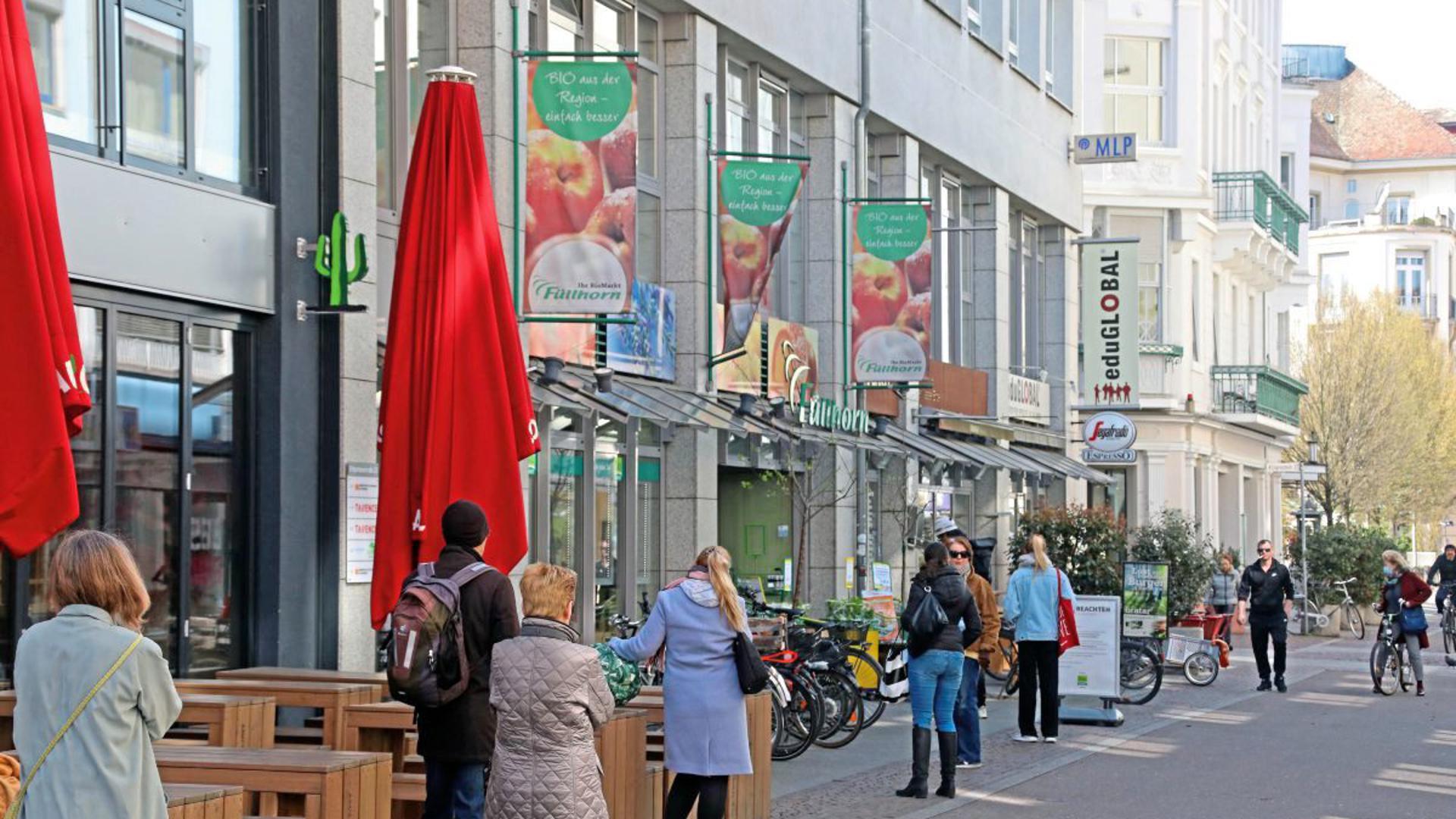 Warten wegen des Coronavirus: Schlange stehen gehört für viele Leute in Karlsruhe zum samstäglichen Eiinkauf dazu.